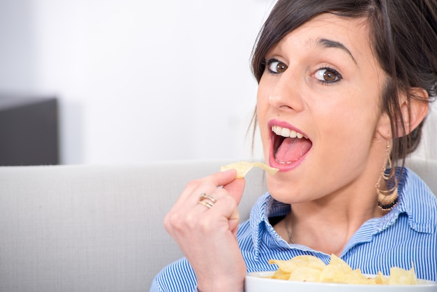 Jeune femme brune mangeant des chips