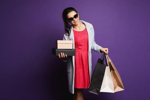 Jeune femme brune en manteau, robe rouge et lunettes de soleil posant avec des sacs à provisions dans ses mains