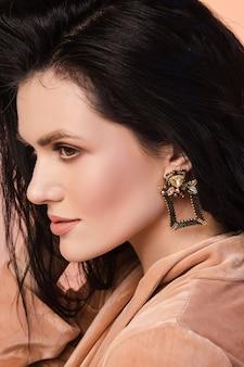 Jeune femme brune avec un maquillage parfait, des cheveux sains et une boucle d'oreille créative élégante. concept de beauté naturelle.