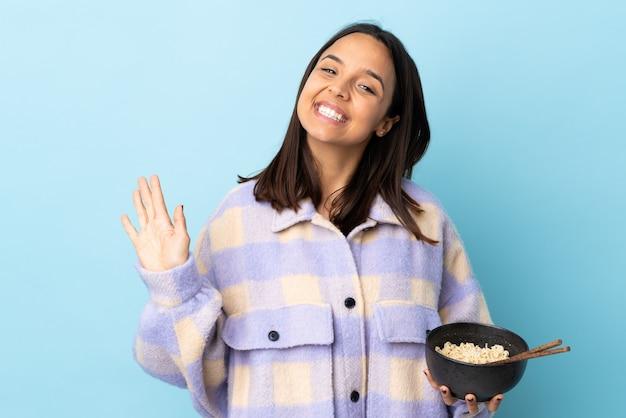 Jeune femme brune métisse sur bleu isolé saluant avec la main avec une expression heureuse tout en tenant un bol de nouilles avec des baguettes.