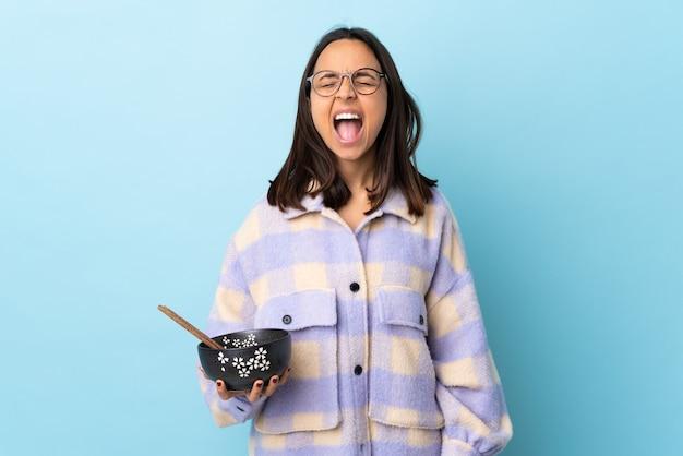 Jeune femme brune métisse tenant un bol plein de nouilles isolé