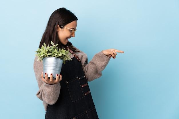 Jeune femme brune métisse tenant une plante sur un doigt pointé bleu isolé sur le côté et présentant un produit.