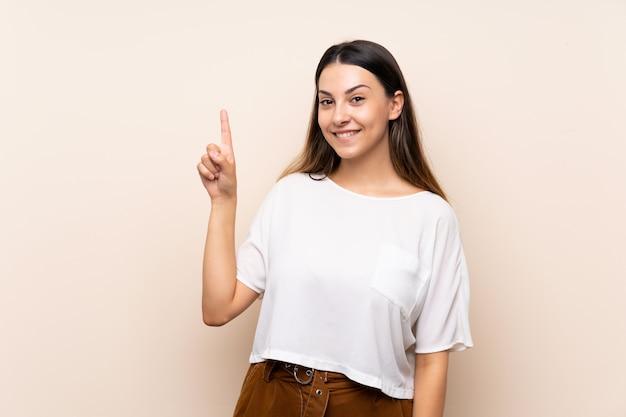 Jeune femme brune montrant et en levant un doigt en signe du meilleur