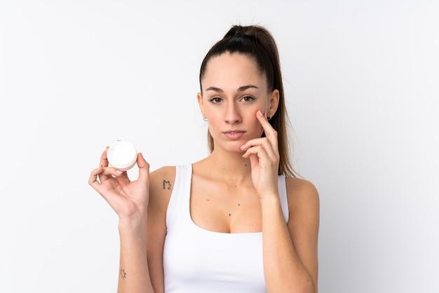 Jeune femme brune sur un mur blanc isolé avec une crème hydratante