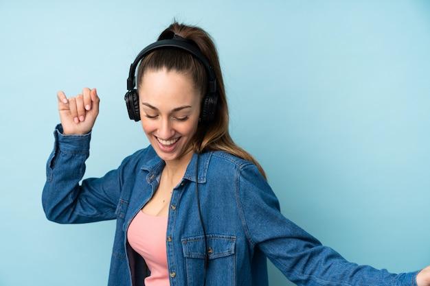 Jeune femme brune sur mur bleu isolé écouter de la musique et de la danse