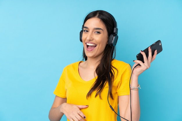 Jeune femme brune sur un mur bleu isolé, écouter de la musique et faire un geste de guitare