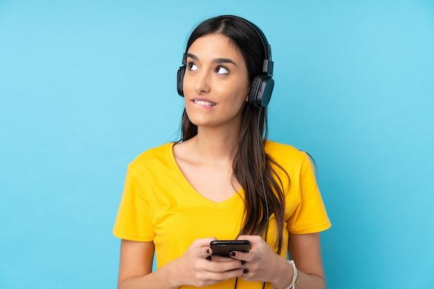 Jeune femme brune sur un mur bleu isolé, écouter de la musique avec un mobile et penser