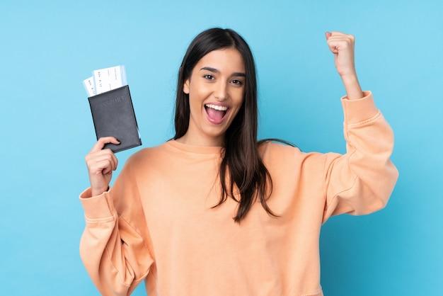 Jeune femme brune sur mur bleu isolé heureux en vacances avec passeport et billets d'avion
