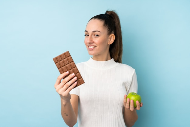 Jeune femme brune sur mur bleu isolé prenant une tablette de chocolat dans une main et une pomme dans l'autre