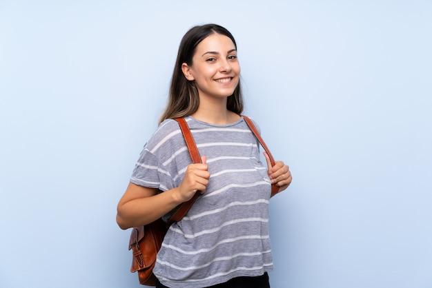 Jeune femme brune sur un mur bleu isolé avec sac à dos