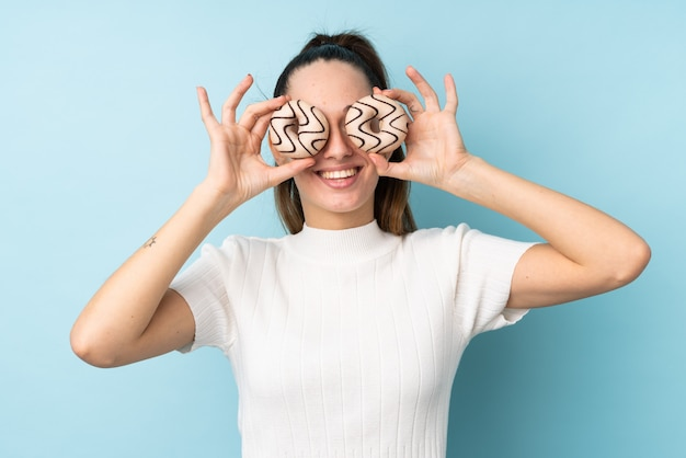 Jeune femme brune sur un mur bleu isolé tenant des beignets dans les yeux