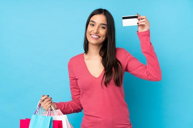Jeune femme brune sur mur bleu isolé tenant des sacs à provisions et une carte de crédit
