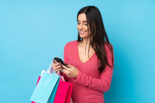 Jeune femme brune sur un mur bleu isolé tenant des sacs à provisions et écrivant un message avec son téléphone portable à un ami