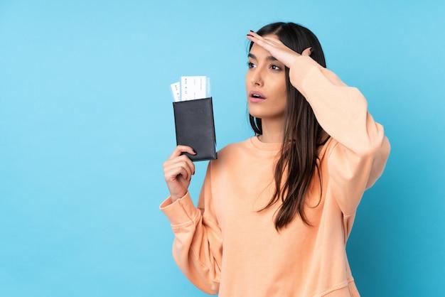 Jeune femme brune sur mur bleu isolé en vacances avec passeport et billets d'avion tout en regardant quelque chose au loin