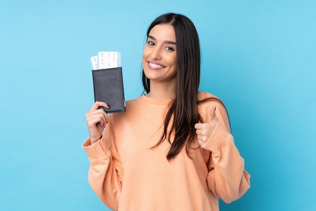 Jeune femme brune sur mur bleu isolé en vacances tenant un passeport et un avion avec le pouce vers le haut