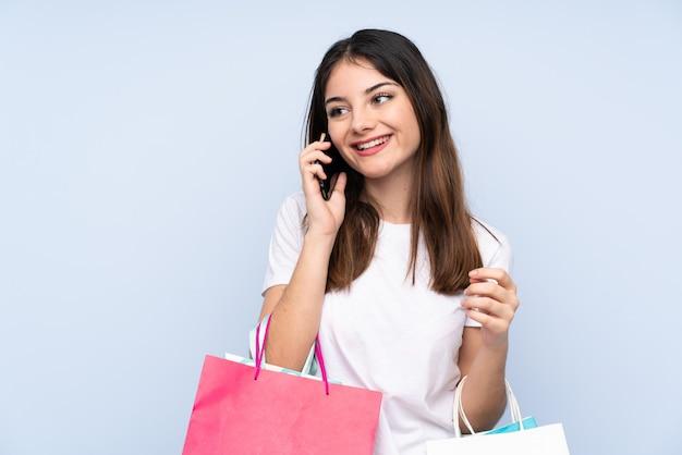 Jeune femme brune sur mur bleu tenant des sacs à provisions et appelant un ami avec son téléphone portable