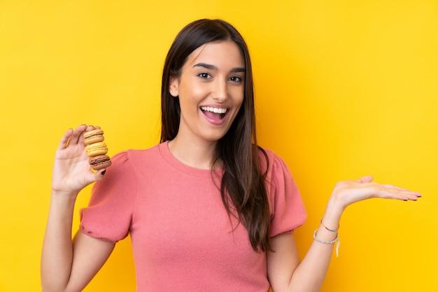 Jeune femme brune sur un mur jaune isolé tenant des macarons français colorés avec une expression choquée