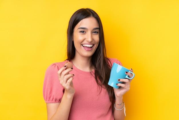 Jeune femme brune sur un mur jaune isolé tenant des macarons français colorés et une tasse de lait