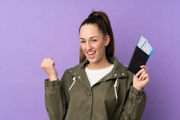 Jeune femme brune sur mur violet isolé heureux en vacances avec passeport et billets d'avion