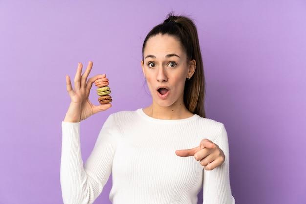 Jeune femme brune sur un mur violet isolé tenant des macarons français colorés et surpris tout en pointant devant