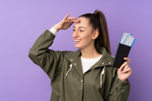Jeune femme brune sur un mur violet isolé en vacances avec passeport et billets d'avion tout en regardant quelque chose au loin