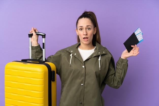 Jeune femme brune sur mur violet isolé en vacances avec valise et passeport et surpris