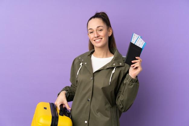Jeune femme brune sur mur violet isolé en vacances avec valise et passeport