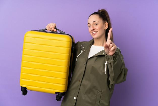 Jeune femme brune sur mur violet isolé en vacances avec valise de voyage et en compter un