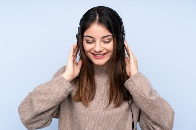 Jeune femme brune sur la musique d'écoute de mur bleu