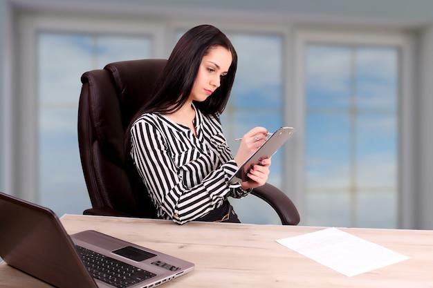 Jeune femme brune avec ordinateur portable au bureau.