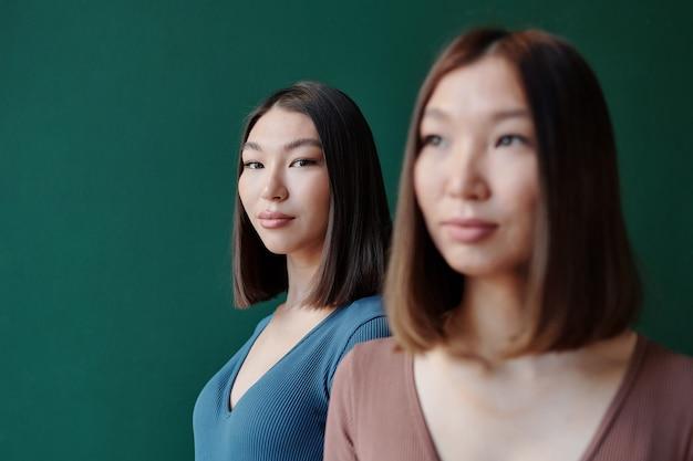 Jeune femme brune d'origine asiatique avec un maquillage naturel vous regarde en se tenant derrière sa magnifique soeur jumelle en studio