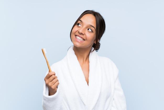 Jeune femme brune en peignoir se brosser les dents sur bleu isolé, levant en souriant