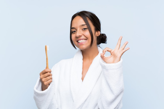 Jeune femme brune en peignoir se brosser les dents sur un mur bleu isolé, montrant un signe ok avec les doigts