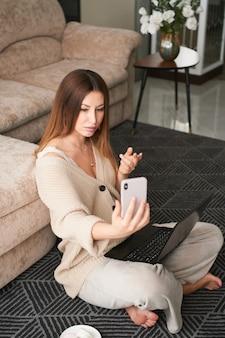 Jeune femme brune pigiste à la maison sur le canapé communique sur un smartphone