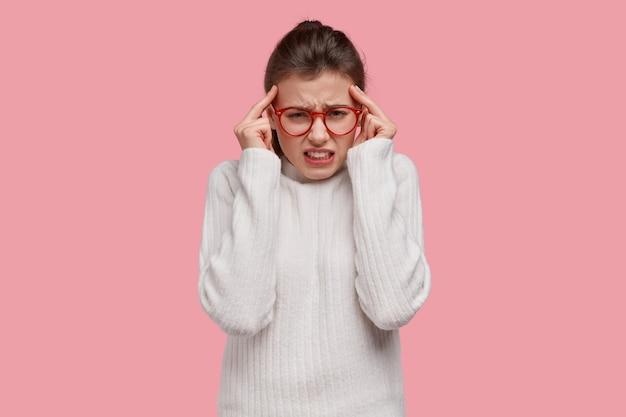 Jeune femme brune portant un pull blanc et des lunettes rouges
