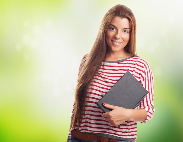 Jeune femme brune posant avec bloc-notes