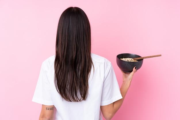 Jeune femme brune en position arrière tout en tenant un bol de nouilles avec des baguettes