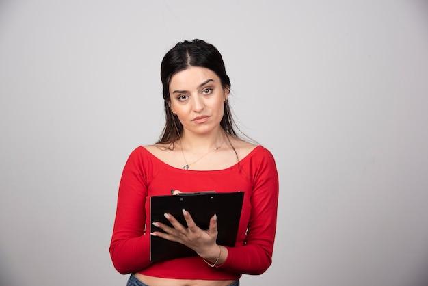 Jeune femme brune avec un presse-papiers en regardant la caméra.