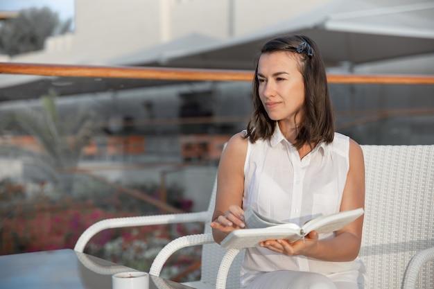 Jeune femme brune profite de la matinée avec une tasse de boisson chaude et un livre dans ses mains