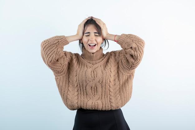 Jeune femme brune en pull en laine debout sur un mur blanc