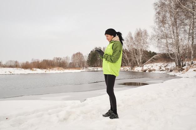 Jeune femme brune avec queue de cheval debout à la rivière et analyse de la route en cours d'exécution sur smartphone