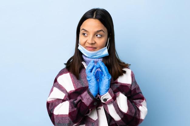Jeune femme brune de race mixte protégeant avec un masque et des gants sur le mur bleu complotant quelque chose