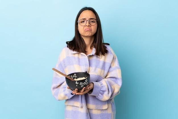 Jeune femme brune de race mixte tenant un bol plein de nouilles sur le mur bleu maintient la paume ensemble