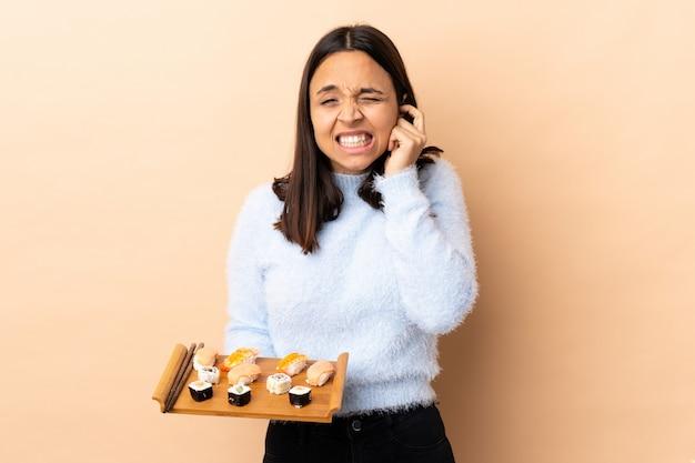 Jeune femme brune de race mixte tenant des sushis sur des oreilles frustrées et couvrant isolées