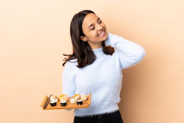 Jeune femme brune de race mixte tenant des sushis sur une pensée isolée une idée