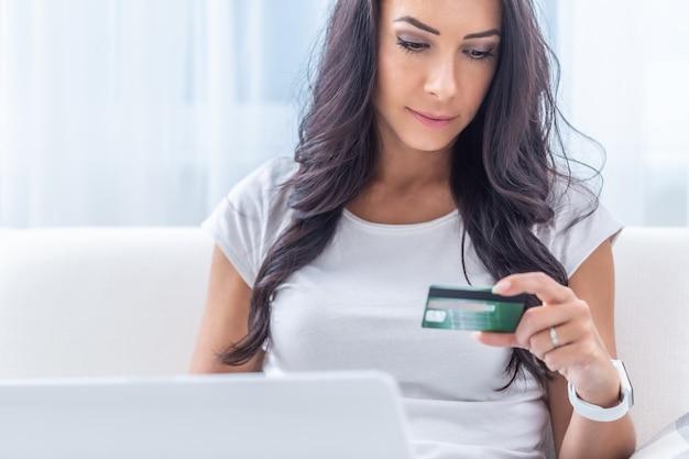 Jeune femme brune regardant la carte de crédit faisant le paiement en ligne dans l'environnement blanc de sa maison.