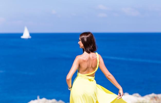 Jeune femme brune en robe d'été jaune debout sur la plage et face à la mer.