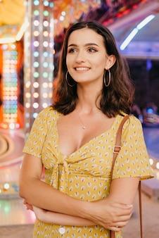 Une jeune femme brune en robe jaune au décolleté plongeant reste entre deux manèges. une fille à la foire de valence le soir.