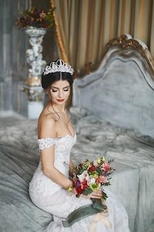 Jeune femme brune en robe de mariée posant sur le lit avec bouquet de mariée