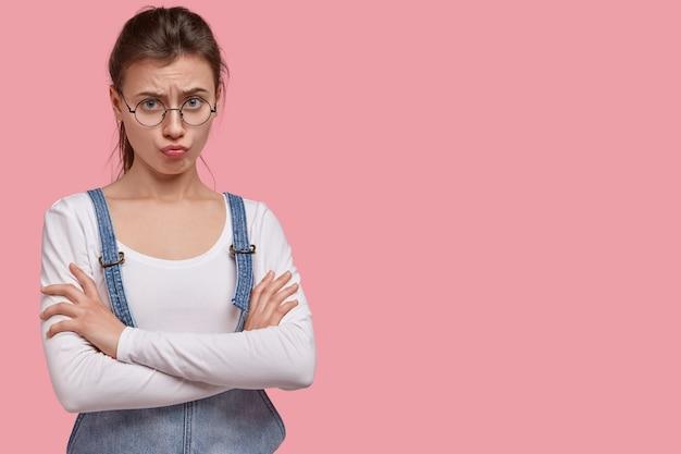 Jeune femme brune en salopette en denim